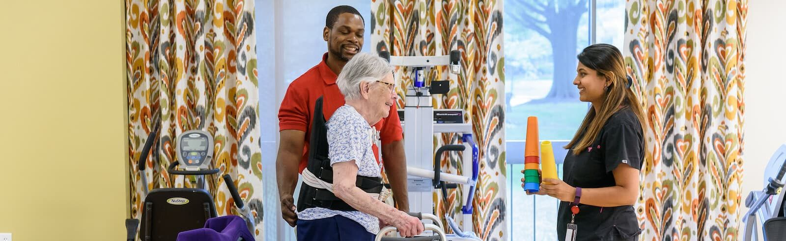 Physical therapists assist senior with walker