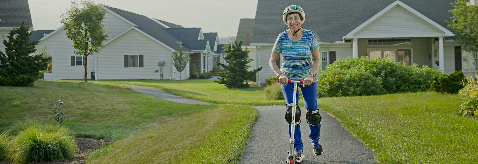 resident riding a scooter ont the walkway of Bethany village