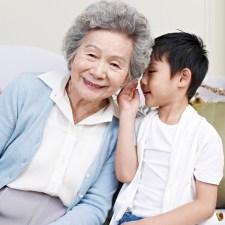 grandson whispering in grandma's ear