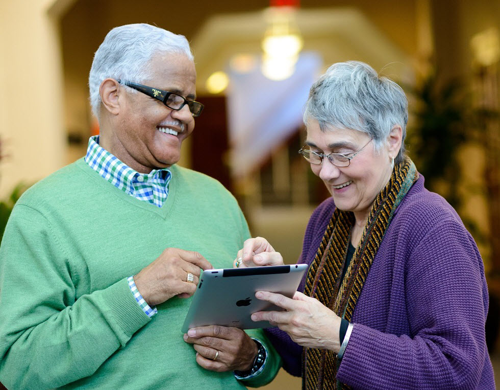 senior couple looking at an iPad