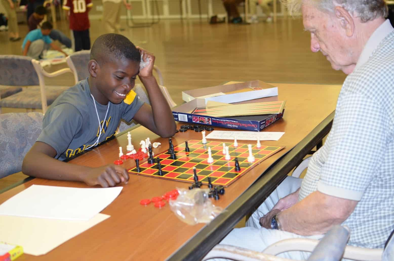 senior playing chess with child