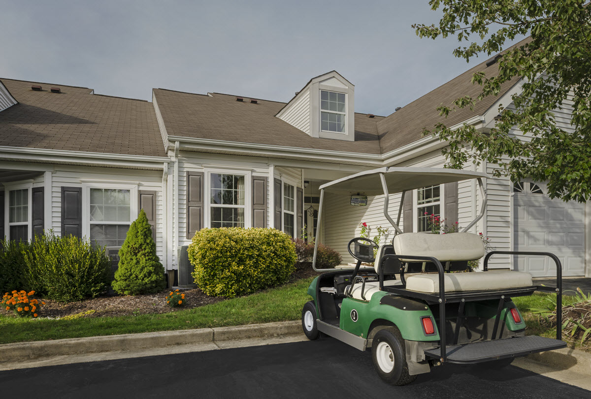 exterior view of cottage home with golf cart