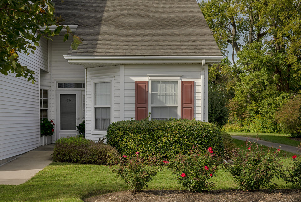 exterior view of cottage home with shrubs