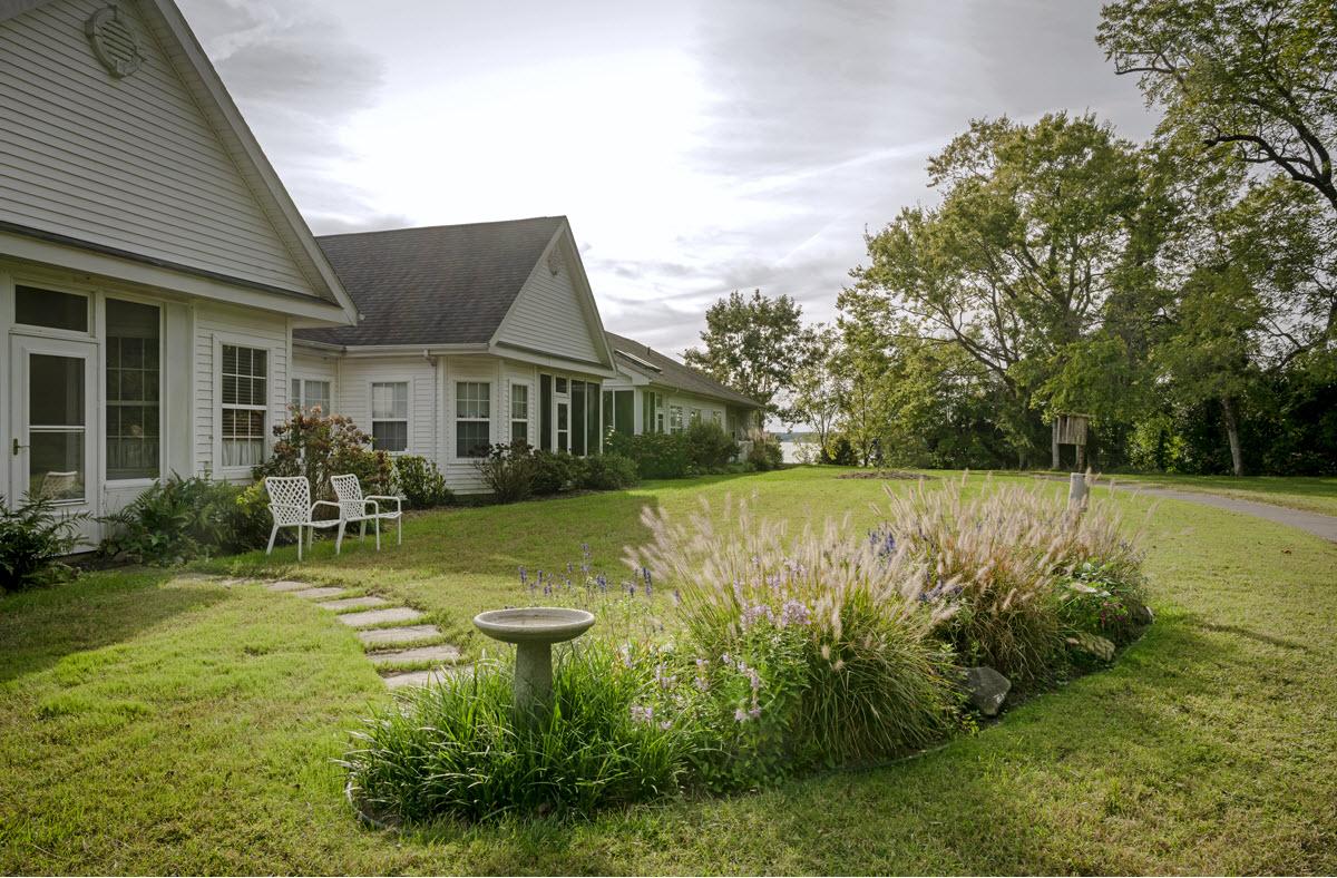 backyard exterior view of cottage home with birdfeeder and garden