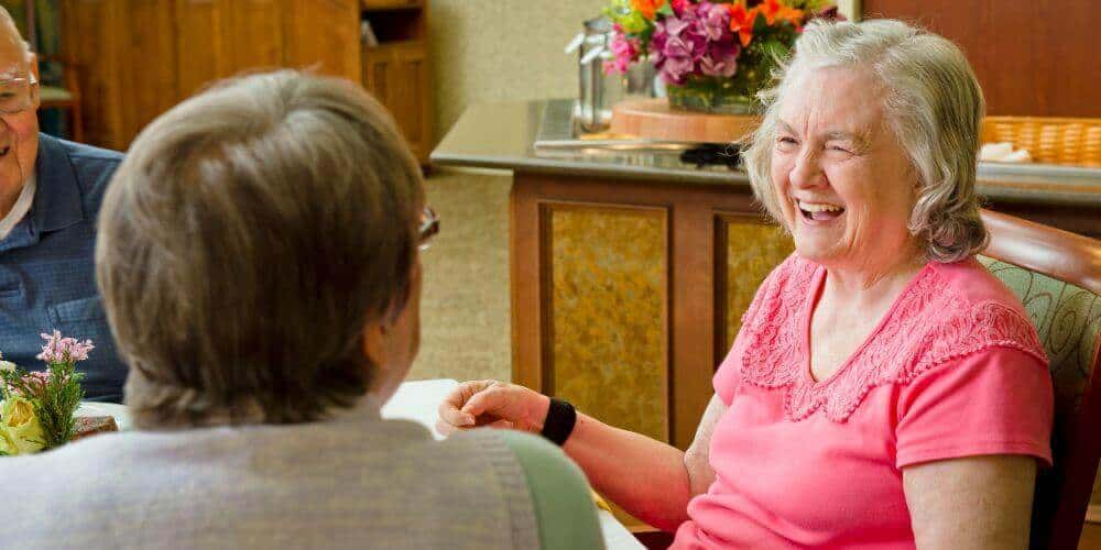 residents laughing together in the dining room