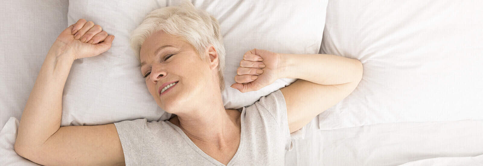 Senior woman stretching in bed after a good night's sleep.