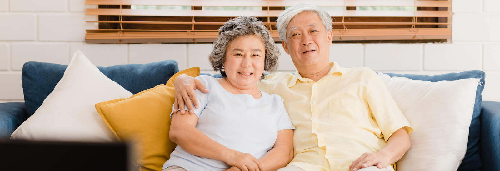 An Asian elderly couple smiling for the camera while sitting on a couch.
