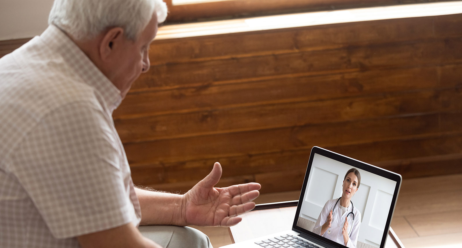 A senior man participating in a virtual doctor appointment.