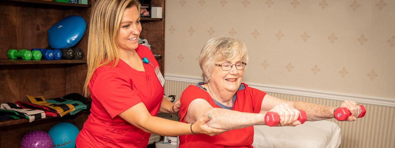 nurse working with resident on rehabilitation