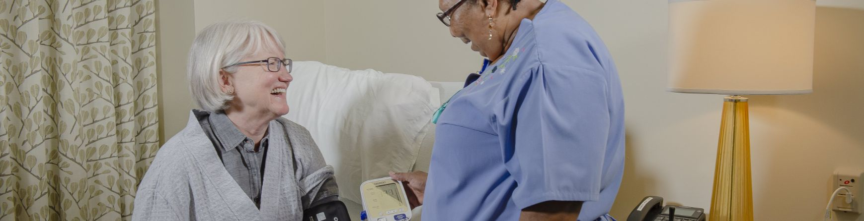 resident getting her blood pressure checked by a nurse