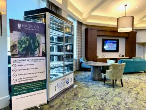 Babylon micro-farm case stands in Bethany Village bistro lobby