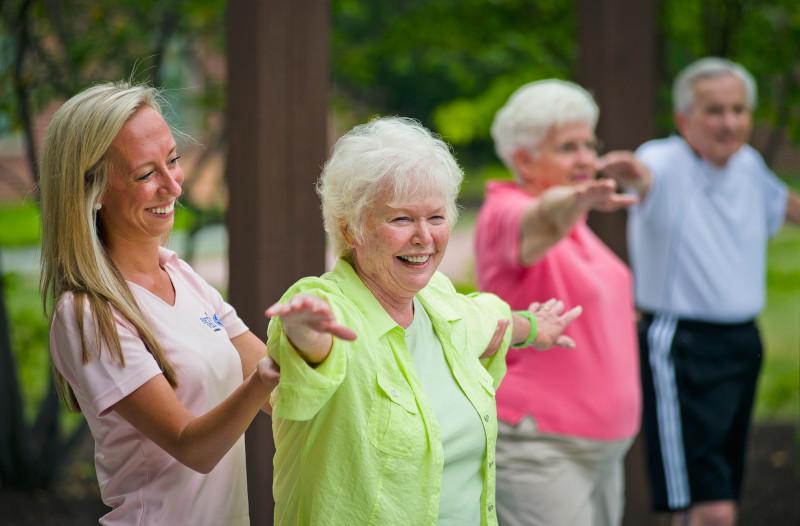 Wellness associate assisting a resident during an outdoor yoga class