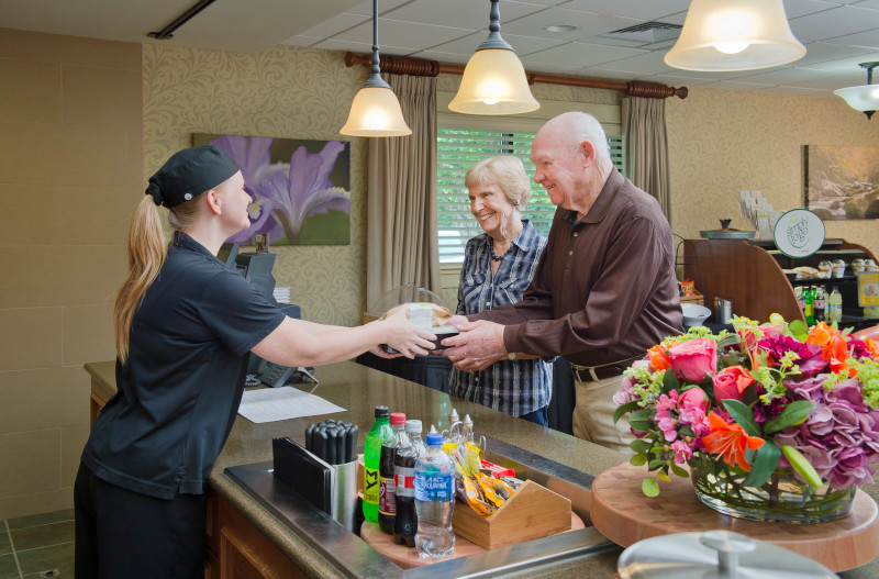 Dining associate serving food to married couple in a cafe