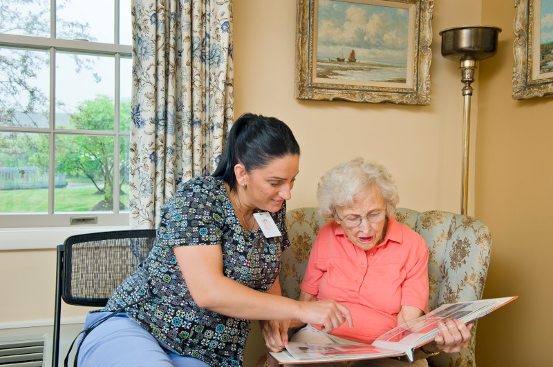 Associate looking at photo album with female resident